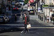 A young man walks by the main street near Oxford Street in London on Thursday, May 28, 2020. The government in Britain eased restrictions across England as a slow loosening of the coronavirus lockdown gets underway, with people now encouraged to return to work if unable to do so from home and unlimited outdoor exercise now allowed. As the row over Prime Minister Boris Johnson's top aide Dominic Cummings' Durham trip, continues, the prime minister's populist appeal has been hammered by the news and members of the public who have seen the evidence and believe that PM Johnson's chief adviser Cummings flouted lockdown rules that the government had imposed on the rest of the country by driving 250 miles (400 kilometres) to his parents' house while he was falling ill with suspected COVID-19. (Photo/ Vudi Xhymshiti)