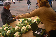 Six months after the fall of the Berlin Wall, an elderly lady is handed her change after buying some cauliflowers at a market stall, on 1st June 1990, in Leipzig, eastern Germany former DDR.