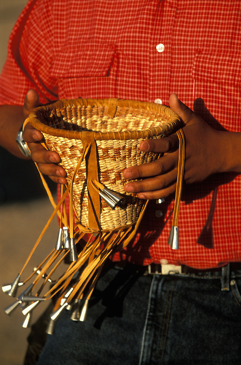 A man holds a basket that contains cigarettes and chewing-gums at a Sunrise Dance on the San Carlos Apache Indian Reservation in Arizona, USA. The Sunrise Dance, a first menstruation rite of an Apache girl, is held during the summer, within one year after the girl has had her first menstruation, and lasts for four days. The ceremony is an enactment of the Apache creation myth and during the rites the girl 'becomes' Changing Woman, a mythical female figure, and comes into possession of her healing powers. The rites are also supposed to prepare the girl for adulthood and to give her a long and healthy life without material wants.