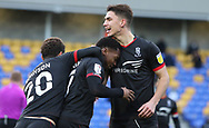 Lincoln City Defender Lewis Montsma (4) and Lincoln City Midfielder Brennan Johnson (20) congratulate Lincoln goal scorer Lincoln City Midfielder Tayo Edun(7) during the EFL Sky Bet League 1 match between AFC Wimbledon and Lincoln City at Plough Lane, London, United Kingdom on 2 January 2021.