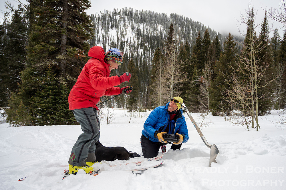 Lynne Wolfe reacts after receiving a live signal on her avalanche beacon from a transmitter box held by Randy Roberts before buring the device last week near the Coal Creek trailhead. The Teton Backcountry Alliance installed eight of the transmitter boxes, which are on loan from Backcountry Access.
