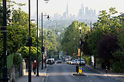 With the London skyline in the far distance, a man walks up the steep gradient of Gypsy Hill in Crystal Palace, on 16th June 2021, in London, England.