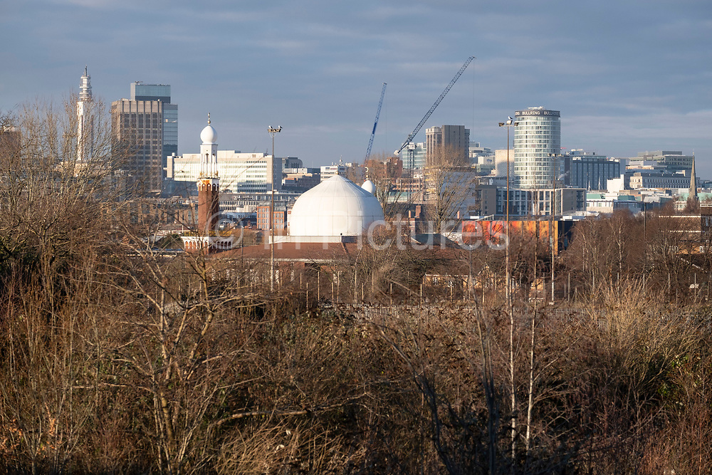 View looking down across overgrown and disused waste ground from Balsall Heath past Birmingham Central Mosque towards the City Centre and the iconic Rotunda building on 7th January 2021 in Birmingham, United Kingdom. Birmingham is undergoing a massive transformation called the Big City Plan which involves the controversial regeneration of the city centre as well as a secondary zone reaching out further. The Big City Plan is the most ambitious, far-reaching development project being undertaken in the UK. The aim for Birmingham City Council is to create a world-class city centre by planning for the next 20 years of transformation.