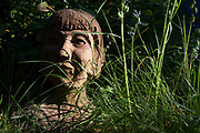 With the UK death toll reaching 38,489, a further 113 victims in the last 24hrs, and the government's pandemic lockdown still in effect, a head sculpture of a young girl rests in long grass in the back garden of a south London property, on 31st May 2020, in London, England.