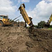 Nederland Lekkerker 25 augustus 2008 20080825 Foto: David Rozing.Dijkversterking Lekkerkerk uitgevoerd in opdracht van Hoogheemraadschap Schieland en de Krimpenerwaard. Graafmachines en vrachtwagens storten grond ter versteviging van de dijk..Schieland en de Krimpenerwaard werkt in Nederlek aan het versterken van de dijk langs de Lek. Het te versterken deel is ruim 5 kilometer lang en beslaat Schuwacht (gedeeltelijk), Voorstraat en Opperduit...Het hele beheersgebied van Schieland en de Krimpenerwaard ligt beneden NAP. Zonder waterkeringen zou er niets dan water zijn, precies zoals het ooit was. Onze voorouders hebben het land op het water veroverd. Wij behouden het voor de toekomst. Dat gaat niet vanzelf. Het klimaat verandert. De zeespiegel stijgt: met 10 tot 90 centimeter in 100 jaar, zeggen de deskundigen. De rivieren zullen vaker veel water ineens afvoeren. En tegelijkertijd daalt de bodem. Dat maakt ons gebied kwetsbaar..Aanleiding voor deze dijkversterking is de vijfjaarlijkse Veiligheidstoetsing in juli 1999. Daarbij heeft 5,7 km lekdijk een onvoldoende gekregen. Ook het tracé Nederlek is niet voldoende stabiel en niet overal hoog genoeg..Om mensen te beschermen tegen overstromingen zijn sterke dijken noodzakelijk. Maar ook ruimte om die dijken te onderhouden, verbreden en versterken. Dat kan grote maatschappelijke gevolgen hebben. Veel mensen wonen of werken op en langs de dijk en hechten daar waarde aan. De dijk is er voor de mens en niet andersom. Tegelijkertijd moet het belang van het individu soms wijken voor het algemeen belang..We beheren, onderhouden en bewaken dijken en waterkeringen. Zwakke waterkeringen worden direct versterkt. We inspecteren ze systematisch en periodiek. In de Keur, het 'wetboek van het waterschap' stellen we regels die schade aan dijken moeten voorkomen. We verlenen vergunningen aan mensen die iets willen op of aan de dijk; een bootje aanleggen, een tuinhuis plaatsen of tuin aanleggen. Dijken dienen op de eerste plaats voor onze