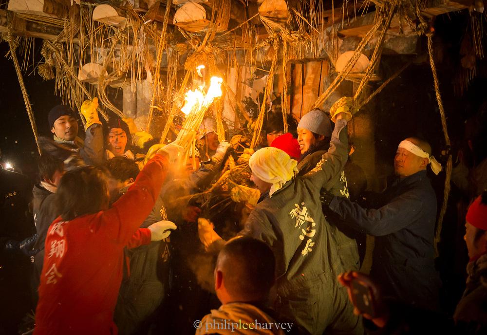 Group of people burning wooden construction at night, Nozawaonsen, Japan