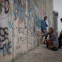 Students paint messages on the separation wall. The Israeli West Bank barrier or wall is a separation barrier in the West Bank. Israel calls it a security barrier while Palestinians and many others call it a racial segregation or apartheid wall. At a total length of 708 kilometres (440 miles) upon completion, the border traced by the barrier is more than double the length of the Green Line, with 15% running along it or in Israel, while the remaining 85% cuts at times 18 kilometres (11 miles) deep into the West Bank, isolating about 9.4% of it, leaving an estimated 25,000 Palestinians isolated from the bulk of that territory.
