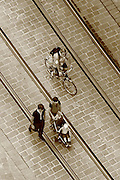 People walk and cycle along the tramlines in the old town of Ghent; seen from the viewing platform of the Belfort
