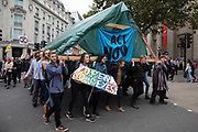 Extinction Rebellion climate change activists carry in and erect a hand made wooden shelter into Trafalgar Square as sites around Westminster are blocked on 8th October 2019 in London, England, United Kingdom. Extinction Rebellion is a climate group started in 2018 and has gained a huge following of people committed to peaceful protests. These protests are highlighting that the government is not doing enough to avoid catastrophic climate change and to demand the government take radical action to save the planet.
