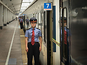A controler staff for the train stands guard at the door of the wagon before departure. Train from Hong Kong to Urumqi, Xinjiang.