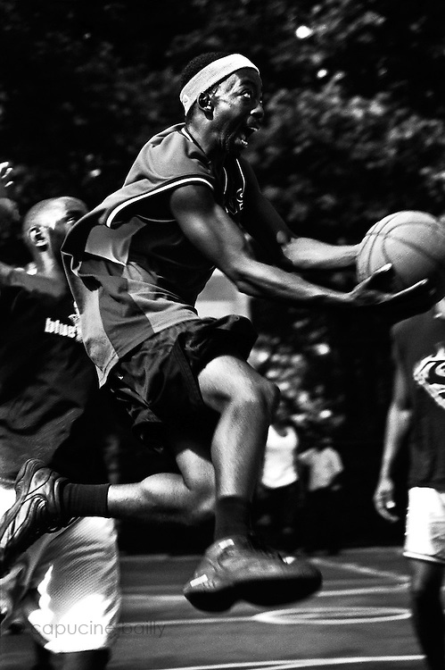 """June 3rd 2004. New York, New York. United States..Located in the heart of Greenwich Village, the West 4th Street basketball Court, known as """"The Cage"""", offers no seating but attracts the best players and a lot of spectators as soon as spring is around the corner..Half the size of a regular basketball court, it creates a fast, high level of play. The more people watch, the more intense the games get. « The Cage » is a free show. Amazing actions, insults and fights sometimes, create tensions among and inside the teams. The strongest impose their rules. Charisma is present..""""The Cage"""" is a microcosm. It's a meeting point for the African American street culture of New York. Often originally from Jamaica or other islands of the Caribbean, they hang out, talk, joke, laugh, comment the game, smoke… Whether they play or not, they're here, inside """"The Cage"""". Everybody knows everybody, they all greet each other, they shake hands and hug: """"Yo, whasup man?"""""""