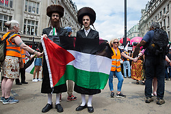 London, UK. 26th June, 2021. Ultra-Orthodox anti-Zionist Haredi Jews from Neturei Karta UK hold a Palestinian flag on the United Against The Tories national demonstration organised by the People's Assembly Against Austerity in protest against the policies of Prime Minister Boris Johnson's Conservative government. The demonstration contained blocs from organisations and groups including Palestine Solidarity Campaign, Stand Up To Racism, Stop The War Coalition, Extinction Rebellion, Kill The Bill and Black Lives Matter as well as from trade unions Unite and the CWU.