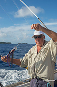 deckhand Walter Morehead sets out lure on charter boat Reel Addiction, Vava'u, Kingdom of Tonga, South Pacific