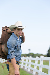 cowboy with a saddle on a ranch