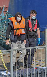 © Licensed to London News Pictures. 12/09/2021. Dover, UK. A Border Force officer helps a migrant ashore as he arrives at Dover Harbour in Kent after crossing the English Channel. Fine weather is expected to see migrants attempt to cross the English Channel to the UK this week.  Photo credit: Stuart Brock/LNP