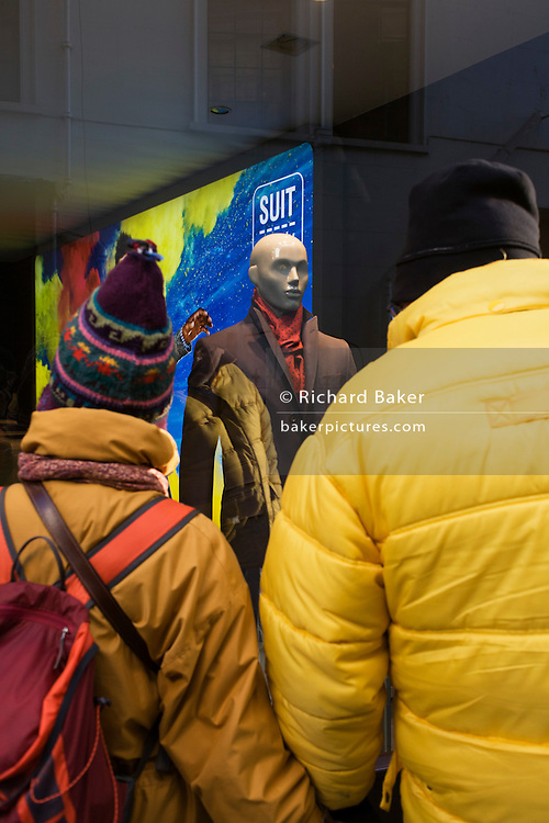 Wearing yellow winter clothing, a tourist couple look in the window of London West End branch of Suit Supply.