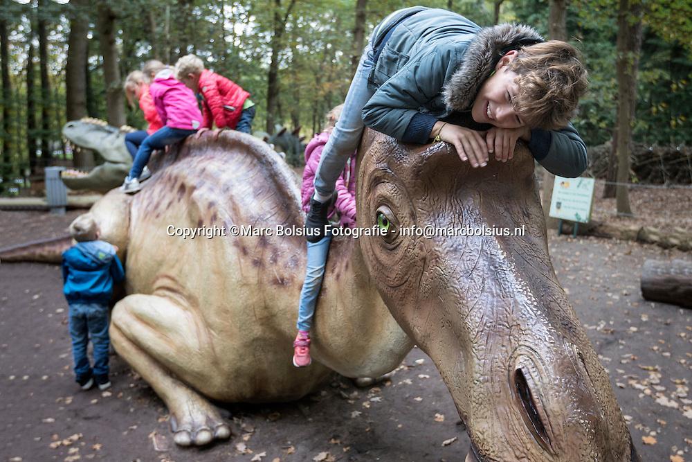 Nederland,  Boxtel, kinderen aan het spelen met een dino in het park.