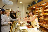 22 JUL 2003, FREITAL/GERMANY:<br /> Angela Merkel, CDU Bundesvorsitzende und CDU/CSU Fraktionsvorsitzende, probiert in einer Baeckerei ein Schinken-Sauerkraut-Brot, waehrend dem Besuch des Weißritzparks mit BUGA-Einkaufscenter<br /> IMAGE: 20030722-01-088<br /> KEYWORDS: Buerger, Bürger, Einzelhandel, Bäckerei