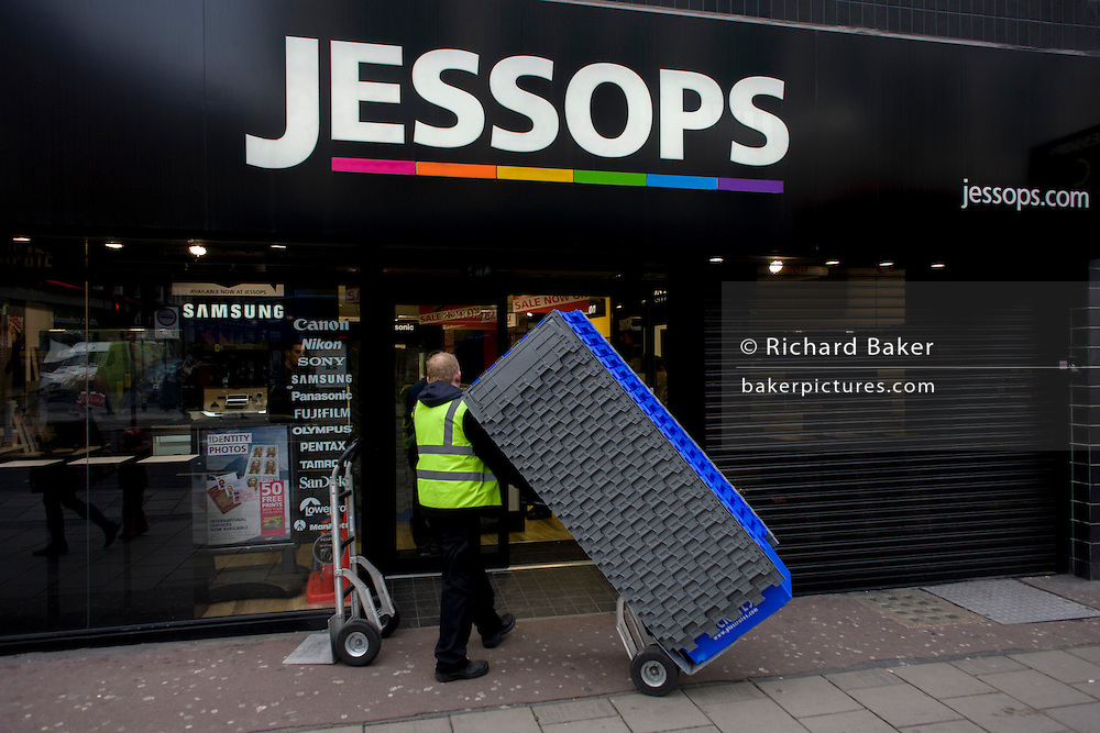 A workman wheels in packing boxes into the Oxford Street store of photo retailer Jessops. Placed into administration by its owners, the high-street branch of UK chain of photographic merchandise and equipment, staff are busy behind shutters packing company assets and stock to be sold elsewhere. Jessops shut all the doors of its 187 UK stores, resulting in the loss of about 1,370 jobs, for the last time. Founded in Leicester in 1935 by Frank Jessop, it has been hit in recent years by increasing competition from supermarkets and internet retailers.