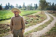 Environmental portrait of Bryan Dickerson by vegetable field.