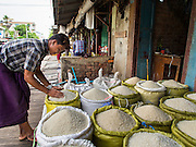08 NOVEMBER 2014 - SITTWE, RAKHINE, MYANMAR:  A man who works in a rice shop sets out the shop's rice in the rice market in Sittwe. Sittwe is a small town in the Myanmar state of Rakhine, on the Bay of Bengal.  PHOTO BY JACK KURTZ