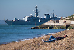 © Licensed to London News Pictures. 02/11/2016. Portsmouth, UK.  A man relaxes in the sun on Southsea beach this morning as the Royal Navy Frigate, HMS Richmond, departs Portsmouth Naval Base.  Today is set to be fine and dry across the South of the UK.  Photo credit: Rob Arnold/LNP
