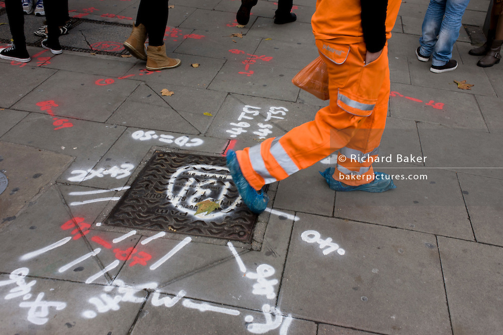 High-visibility workman walks over pavement markings.