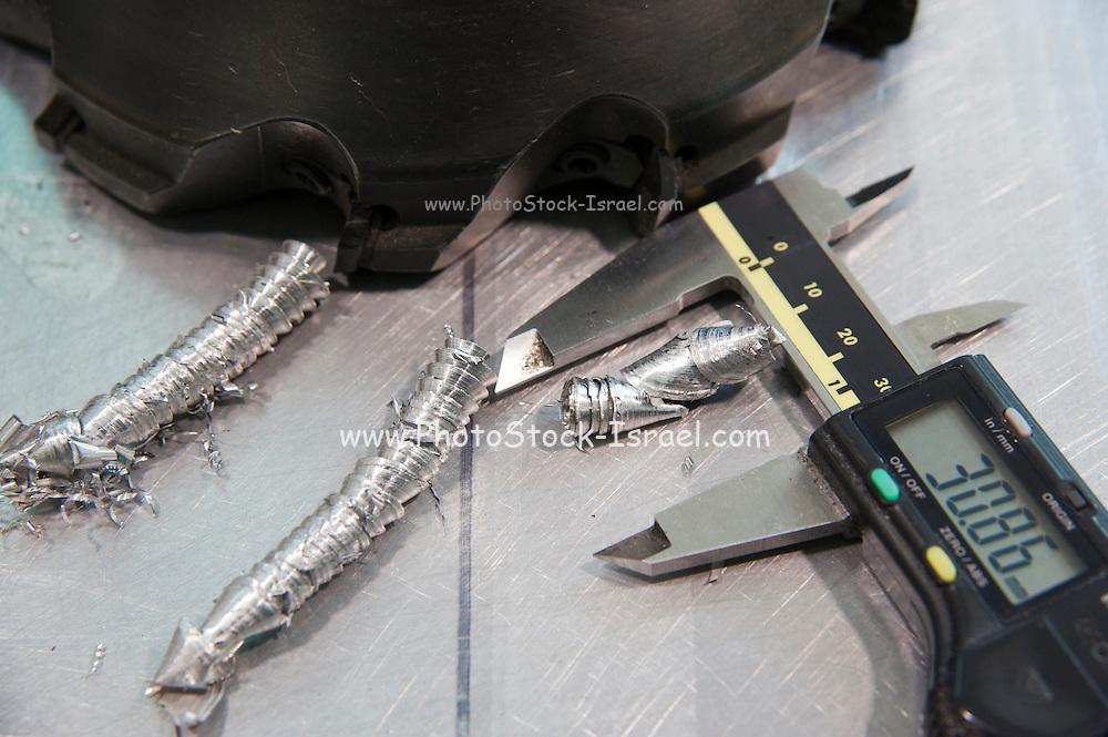 Metal tooling shop floor concept with micrometer calliper and metal shavings