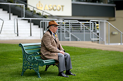 A general view of a spectator sat on a bench during Royal Ascot Trials Day at Ascot Racecourse.