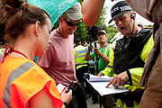 Balcombe, West Sussex. Site of Cuadrilla drilling. Demonstration against fracking 18.08.2013. A policeman holds a Section 14 order as he tells protesters to move.