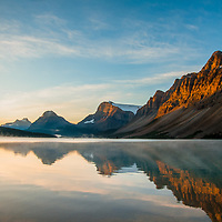 Mist rises over Bow Lake as dawn breaks on Mount Andromache, Mount Hector, Bow Peak, Bow Crow Peak and Crowfoot Mountain in Banff National Park, Alberta, Canada.