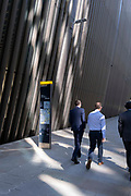 Businessmen walk past a map of the City of London which is positioned beneath corporate office architecture, in the capitals financial district, on 24th September 2021, in London, England.