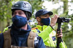 Aylesbury Vale, UK. 1st October, 2020. A Thames Valley Police officer, working with bailiffs from the National Eviction Team, carries out surveillance on anti-HS2 activists during evictions from a wildlife protection camp in the ancient woodland which inspired Roald Dahl's Fantastic Mr Fox at Jones' Hill Wood. Around 40 environmental activists and local residents, some of whom living in makeshift tree houses about 60 feet above the ground, were present during the evictions at Jones' Hill Wood which had served as one of several protest camps set up along the route of the £106bn HS2 high-speed rail link in order to resist the controversial infrastructure project.
