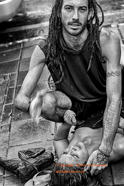 Bangkok Streets (B&W): A young man in dread locks holds down a distressed, beautiful woman and awaits the police and an ambulance; claiming he was owed both his room key and money, near Khaosan Road - Bangkok Thailand.