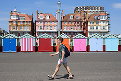 © Licensed to London News Pictures. 03/07/2018. Hove, UK. A young man walks past colourful beach huts on the seafront at Hove, East Sussex on the south coast of England, as a heatwave continues across the UK. Photo credit: Ben Cawthra/LNP