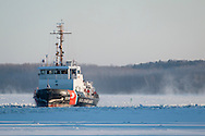 The United States Coast Guard cutter Sturgeon Bay breaks ice in the shipping channel on the Hudson River near Hudson, New York. The 140-foot Bay-class cutter has a 17-person crew.