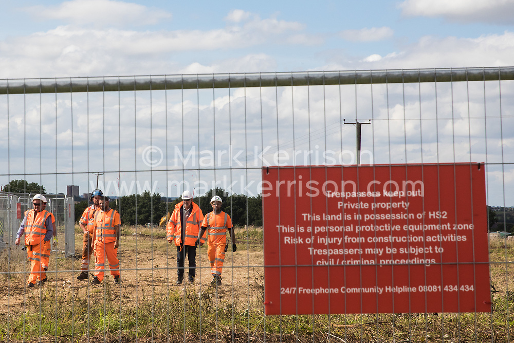 Offchurch, UK. 24th August, 2020. HS2 workers monitor anti-HS2 activists after some had occupied mature oak trees and a trailer transporting wood chip in order to try to prevent or delay tree felling alongside the Fosse Way in connection with the HS2 high-speed rail link. The controversial HS2 infrastructure project is currently expected to cost £106bn and will destroy or significantly impact many irreplaceable natural habitats, including 108 ancient woodlands.