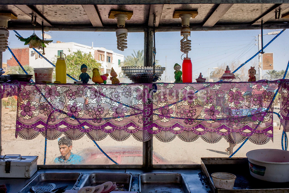Detail of a street vendor's food stall in a street cafe in Kharga Oasis in the Western Desert, Egypt. The head and face of a young man is seen through the window and the heat of mid-day can be imagined in the bright background of Kharga town centre. The Western Desert covers an area of some 700,000 km2, thereby accounting for around two-thirds of Egypt's total land area. Dakhla Oasis is one of the seven oases of Egypt's Western Desert (part of the Libyan Desert). It lies in the New Valley Governorate, 350 km (220 mi.) and measures approximately 80 km (50 mi) from east to west and 25 km (16 mi) from north to south.