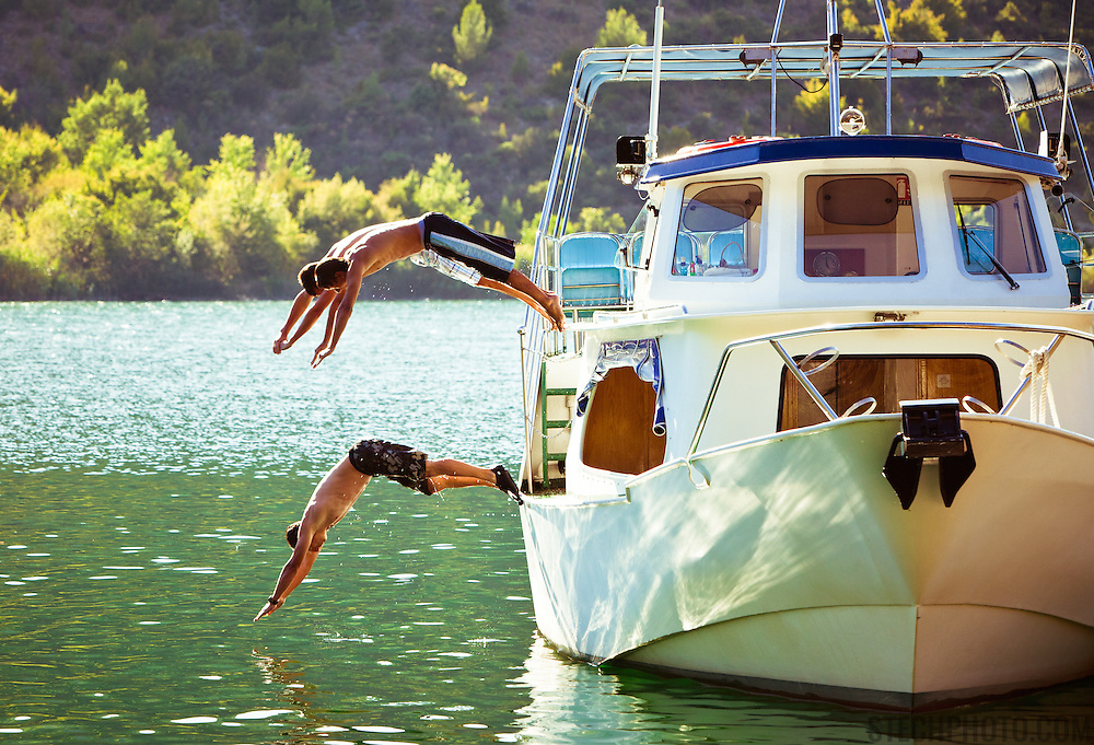 Three men diving into the Krka River in the Krka National Park on a hot summer day in Croatia.