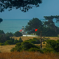 Pine and Cypress trees frame the Point Cabrillo Light Station on the California coast in Mendocino County.