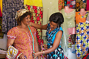 """Rahab Mbuba (left) measuring a customer for a new outfit.<br /> <br /> Rahab, also known as 'Mama B"""", set up and now runs a tailoring business, designing and making clothes.<br /> <br /> She attended MKUBWA enterprise training run by the Tanzania Gatsby Trust in partnership with The Cherie Blair Foundation for Women."""