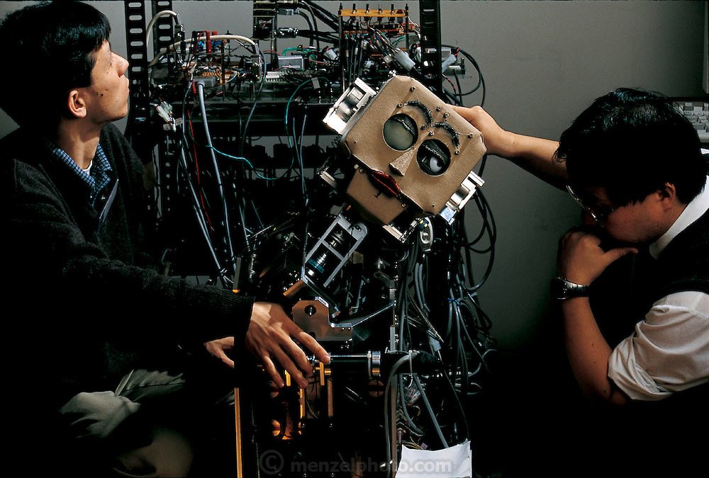 In a situation all too familiar to robotics researchers, Atsuo Takanishi (on right) is trying to make his creation work. His research team's robot, WE-3RIII (Waseda Eye Number 3 Refined Version III) can follow a light with its digital-camera eyes, moving its head if needed. In the laboratory the robot worked perfectly, its movements almost disconcertingly lifelike. But while being installed at a robot exhibit in Tokyo, WE-3RIII inexplicably and violently threw back its head, tearing apart its own wiring. Now Takanishi and one of his students are puzzling over the problem and will solve it only in the early hours of the morning before the exhibit opened. Japan.From the book Robo sapiens: Evolution of a New Species, page 40-41..
