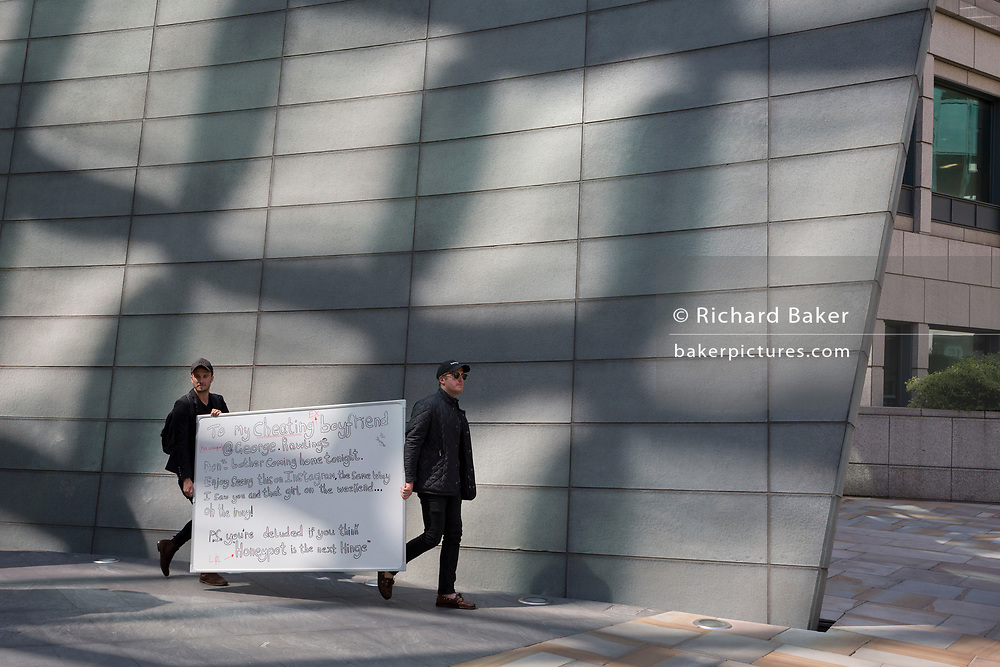 Two men carry a white-board through Broadgate as part of a new Dating app start-up's PR stunt purporting to be written by a jealous lover to her cheating partner who works nearby in the City of London, the capital's financial district - aka the Square Mile, on 8th August, in London, England.
