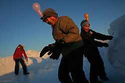 In play, school children slip and slide on the ice in front of the small Inuit community of Qeqertat, Greenland. A changing climate - which shows itself in warming temperatures, earlier summers, later winters, and shrinking and thinning sea ice - threatens the livelihoods and traditions of some of the last subsistence hunters on Earth, the Polar Inuit communities of far Northwest Greenland.