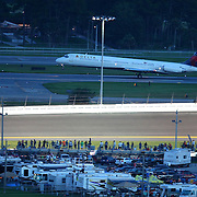 An airliner takes off from the Daytona airport during the NASCAR Coke Zero 400 Sprint series auto race at the Daytona International Speedway on Saturday, July 6, 2013 in Daytona Beach, Florida.  (AP Photo/Alex Menendez)