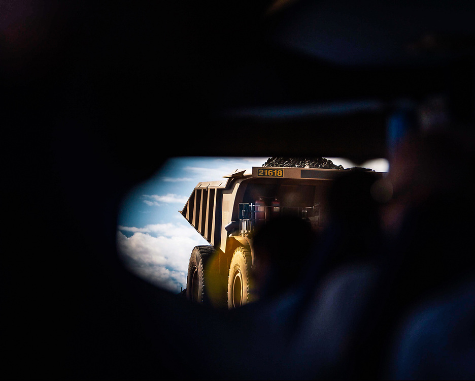 An iron ore haulage truck is reflected in the rear vision mirror of a Light Vehicle (LV) at a mine site in the Pilbara region of Western Australia.