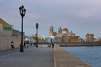 The Cathedral of Cadiz at sunset attracts people to the ocean-side walkway to gaze at the domed structure.