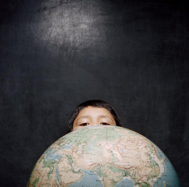 Young boy, 5-8 years, peeking over globe