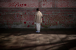 © Licensed to London News Pictures. 08/04/2021. London, UK. A member of the public contemplates a section of the National Covid Memorial Wall, which has now been completed with approximately 150,000 hearts painted on the Thames Embankment opposite the Houses of Parliament to remember those who lost their lives to Covid-19. Members of the public are invited to walk the length of the memorial, and campaigners are asking Prime Minister Boris Johnson to make the memorial permanent. Photo credit: Rob Pinney/LNP