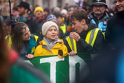 © Licensed to London News Pictures. 28/02/2020. Bristol, UK. Environmental activist GRETA THUNBERG (in yellow coat) holds the banner at the front of the march at the Bristol Youth Strike 4 Climate with many thousands of people through the city centre. Greta Thunberg started the Youth Strike 4 Climate protest movement in her home country of Sweden when she sat alone outside the Swedish parliament, eventually paving the way for the Fridays for Future movement across the world. Thousands of people are expected to attend the event in Bristol with many roads closed in the city centre. In 2018 Bristol was the first city to declare a climate emergency and also the first to declare an ecological emergency just four weeks ago. Photo credit: Simon Chapman/LNP.